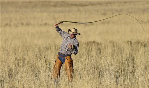 A riders cracks his whip before the start of the annual bison roundup Friday, Oct. 23, 2015, on Antelope Island, Utah. Utah State Parks workers are moving the animals from across the island on Friday so they can be weighed, tagged and given health checkups. Antelope Island is on the Great Salt Lake, about 50 miles north of Salt Lake City. (AP Photo/Rick Bowmer)