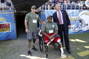 Denver Broncos executive vice president John Elway, right, poses with wounded Marine veterans Cpl. Michael Fox, left, and Cpl. Toran Gaal, center before an NFL football game between the Denver Broncos and the San Diego Chargers Monday, Oct. 15, 2012, in San Diego. (AP Photo/Lenny Ignelzi )