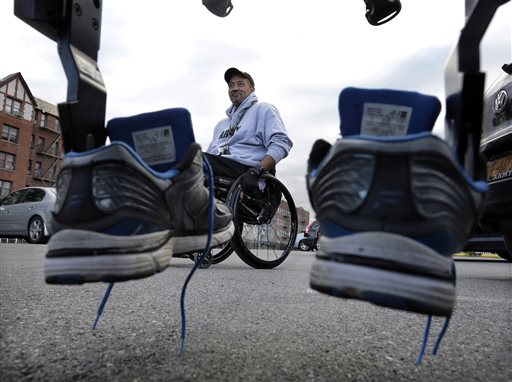 Paralyzed Army veteran Gene Laureano's sneakers are mounted on a ReWalk device as he prepares to use the machine to walk Wednesday, Dec. 16, 2015, in Bronx, N.Y. ReWalk Robotics CEO Larry Jasinski said a dozen VA centers are expected to start training staff to provide the system. The program will likely be expanded in the future. (AP Photo/Mel Evans)