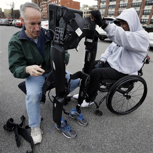 ReWalk Robotics service engineer Tom Coulter prepares a ReWalk device to allow paralyzed Army veteran Gene Laureano to walk Wednesday, Dec. 16, 2015, in Bronx, N.Y. The Department of Veterans Affairs has agreed to pay for robotic legs that could allow scores of paralyzed veterans with spinal cord injuries to walk again. (AP Photo/Mel Evans)