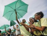 Randle Highlands Elementary School fourth graders, center, from left, Zaria Russell, Zani La McElwain, and Kelsi Williams raise their umbrella while assembling into a living version of the National Park Service's iconic Arrowhead emblem, near the Washington Monument on the National Mall in Washington, Thursday, Aug. 25, 2016. More than 1,000 participants used brown, green and white umbrellas to create the emblem during an event that took place on the 100th anniversary of the creation of the National Park Service. They also posed for a group photo that was being taken from a helicopter hovering overhead. (AP Photo/Pablo Martinez Monsivais)