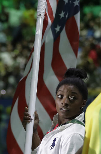 Simone Biles carries the flag of the United States during the closing ceremony in the Maracana stadium at the 2016 Summer Olympics in Rio de Janeiro, Brazil, Sunday, Aug. 21, 2016. (AP Photo/David Goldman)