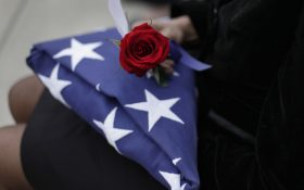 Amelia Dukes-Hutton holds a rose and the flag from the casket of her brother, Roland Burke Dukes, during a memorial service and burial at Great Lakes National Cemetery in Holly Township, Mich., Thursday, Sept. 11, 2014. (AP Photo/Paul Sancya)