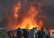 """Thick smoke and flames rise from amidst the tents after fires were started in the makeshift migrant camp known as """"the jungle"""" near Calais, northern France, Wednesday, Oct. 26, 2016. Firefighters have doused several dozen fires set by migrants as they left the makeshift camp where they have been living near the northern French city of Calais. (AP Photo/Emilio Morenatti)"""