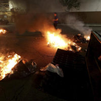 Multiple fires are lit in dumpsters and trash cans during protests in downtown Oakland, Calif., late Tuesday, Nov. 8, 2016. President-elect Donald Trump's victory set off multiple protests. (Jane Tyska/Bay Area News Group via AP)