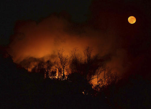 In this Tuesday, Nov. 15, 2016, photo, a wildfire burns as it approaches Bat Cave, N.C. Thick smoke has settled over a wide area of the southern Appalachians, where dozens of uncontrolled wildfires are burning through decades of leaf litter, and people breathe in tiny bits of the forest with every gulp of air. (Patrick Sullivan/The Times-News via AP)