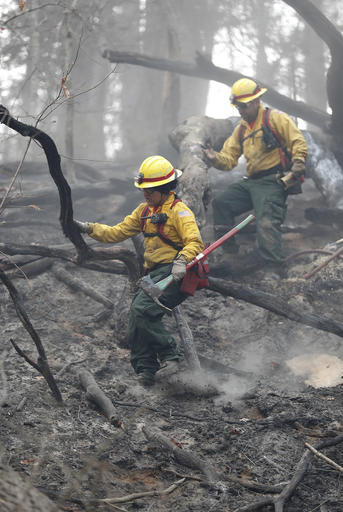 In a Tuesday, Nov. 15, 2016 photo, firefighters Valarie Lopez is followed by Mark Tabaez as they climb down a hill after cooling hot spots from a wildfire that burned a hillside in Clayton, Ga. There were more than 30 uncontained large fires burning across the southeast, federal officials said in a Wednesday update. Fires across the region have burned a total of 128,000 acres, or about nine times the size of Manhattan.(AP Photo/John Bazemore)