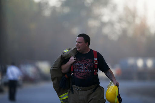 An Alabaster firefighter walks near the scene of an explosion of a Colonial Pipeline, Monday, Oct. 31, 2016, in Helena, Ala. Colonial Pipeline said in a statement that it has shut down its main pipeline in Alabama after the explosion in a rural part of the state outside Birmingham. (AP Photo/Brynn Anderson)