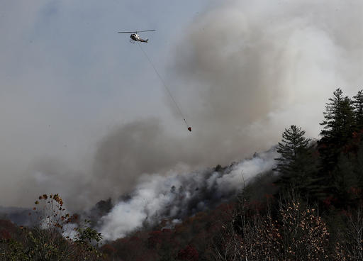 A helicopter works dropping water on the Rock Mountain wildfire as it approaches homes, Wednesday, Nov. 16, 2016, in Tate City, Ga. (Curtis Compton/Atlanta Journal-Constitution via AP)