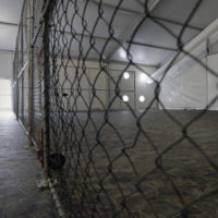 A U.S. Customs and Border Protection agent stands at the door to a U.S. Customs and Border Protection temporary holding facility near the Donna-Rio Bravo International Bridge, Wednesday, Dec. 7, 2016, in Donna, Texas. The tent facility, primarily to be used as a temporary holding site for children and families who have entered the county illegally, is due to open Friday and process up to 500 people a day. (AP Photo/Eric Gay)