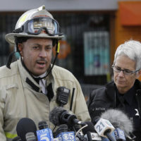Oakland fire deputy chief Darren White, left, speaks next to Oakland Police officer Johnna Watson at a news conference near the site of a warehouse fire in Oakland, Calif., Tuesday, Dec. 6, 2016. The fire erupted Friday, Dec. 2, killing dozens. (AP Photo/Jeff Chiu)
